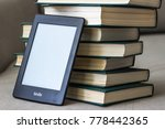 Small photo of CHERKASSY, UKRAINE - APRIL 23, 2016: Amazon Kindle paperwhite reader over big stack of books.