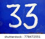 Small photo of The figure is thirty-three. White number on a bright blue background, shown close-up.