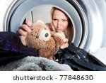 young woman picking a teddy bear from a washing machine - stock photo
