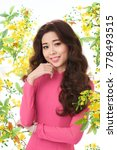 Small photo of Waist-up portrait of attractive Asian woman wearing pink dress looking at camera with toothy smile while standing against white background decorated with ochna tree