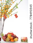 Small photo of Well-known attributes for Lunar New Year celebration: glass vase with ochna tree branches, ripe fruits, traditional decorations, isolated on white background