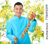 Small photo of Joyful Vietnamese man wearing traditional costume holding decoration for Tet holiday in hands while posing for photography, blooming ochna tree on background