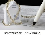 Small photo of white small paper house tied with chain to the pen signing the contract, loan indebtedness concept, close up, selective focus , blurred background
