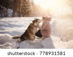 Stock photo girl is playing with dog in snow new year s holidays rest in nature in winter 778931581