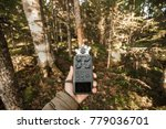 Small photo of Record sounds and noise of the forest on a digital hand-held microphone. A man holds an audio recorder on the outstretched hand in the thicket of the forest.