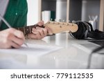 Small photo of Close up of musician writing music on paper. Focus on his fingers doing accord on guitar