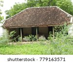 Small photo of An old vintage house in india with clay ceramic Pantile roof, surrouded by trees and greenery