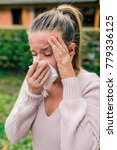 Small photo of Young woman blowing her nose. allergic rhinitis. Disease, sickness, allergy, malady problem concept. Woman wiping her nose with hygienic paper tissue having cold and feeling bad. Woman has sneezing