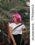Small photo of girl with glasses.woman in the jungle. girl in white t-shirt on head pink wig with bangs. plants on the background