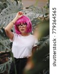 Small photo of girl in glasses. woman in the jungle. girl in white t-shirt on head pink wig with bangs. plants on the background