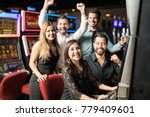 Group of five friends having a good time together while they play some slots in a casino and they win some money - stock photo