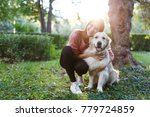 Stock photo photo of woman hugging dog on lawn 779724859