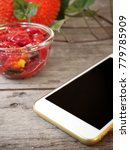Small photo of Smart phone with gac fruit