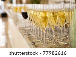 Rows of champagne flutes on bar counter, shallow focus - stock photo