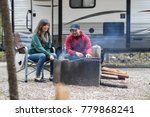 A young attractive couple relaxing at their camp site while RV camping