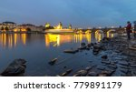 The Charles Bridge day to night transition timelapse over the Vltava River reflected in water in Prague, Czech Republic. Illuminater buildings and old town tower