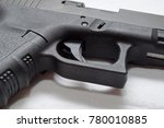 Small photo of A close up of a black semi automatic pistol, showing the trigger, trigger guard, grip and ejection port