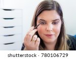 woman applying makeup in her... | Shutterstock . vector #780106729