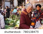 Small photo of Lincang, Yunnan Province, China-25.01.2017- Elderly woman buys fruits on local makeshift street market.