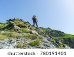 Small photo of One backpacker hiking uphill on steep rocky slope towards the mountain summit. Concept of reaching the goal and conquering the success. Summer adventures and exploration on the Alps.