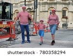 Small photo of Bath, UK - September 28, 2012: A family dress up as the fictional character Wally from the British puzzle book series Where's Wally by author and illustrator Martin Handford.