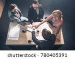 Small photo of Top view cheerful female and male colleagues holding arms together while sitting at table in office. Profession and relation concept