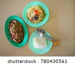 Small photo of Thai local traditional Isaan Northeast cuisine set of Som Tam Poo, spicy papaya salad with black crab, Larb Moo, raw stir fried pork with herb, and sticky rice in plastic bag, green plastic plates