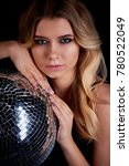 Small photo of The blonde laying in the style of Abba holds a disco ball. The era of disco. Night club, dancing