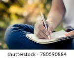 Stock photo close up young women writing on notebook in park concept in education and knowledge 780590884