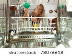 young woman seen from inside of a dish washer - stock photo