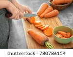 Woman Cutting Carrot On Table ...