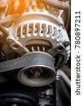 Small photo of details of car engine, alternator or electrical generator with sunlight effect