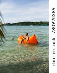 Small photo of Young blonde man, boy at the beach with Lazy Inflatable Air Bed, hammock, couch camping. Lounger Sofa Beach Chair Portable Sleeping Bag Mattress. Relax, vacation, travel. Asia. Thailand