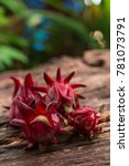 Small photo of Roselle - Fresh Roselle on an old wooden table with green nature background. Closeup, Selective focus.