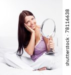 Stock photo beautiful young brunette woman with a mirror on the bed at home 78116638