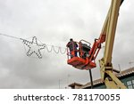 Small photo of Two municipal service electricians who install Christmas electric bulbs on a crane in a city in Spain