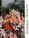 Small photo of Fresh flower delivery at the florist shop: different flowers stocked up together, orange red and paster colours; different types of roses and ranunculus with eucalyptus on the background