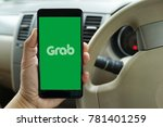 Small photo of PENANG, MALAYSIA - NOVEMBER 14, 2017: A man is using Grab application on smartphone. Grab is a Malaysian technology company that offers ride-hailing and logistics services through its app.