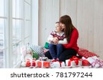 a little son holds a gift in a... | Shutterstock . vector #781797244