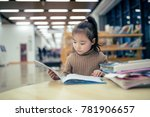Small photo of The lovely young asian girl who reads books in the library