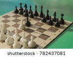 Small photo of Black and white chess on a cardboard box. Game pawns begin. Green background, side sunlight.