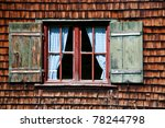 Ancient window on log house wooden wall - stock photo