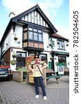 Small photo of LYNDHURST ENGLAND -OCT 14 : Asian female tourist in front of greene king accommodation atmosphere represent british tourism on October 14, 2015 in New Forest Lyndhurst , England.