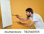 Small photo of painter draws on canvas on a yellow background, draw, drawing, paint, art