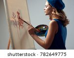 Small photo of painter draws on canvas holds a palette on a gray background, paint, drawing, draw
