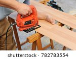 carpenter cutting a wooden...