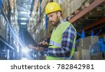 Small photo of Warehouse Worker Uses Laptop. He's Standing in the Middle of a Big Distribution Center with Big Storage Racks and Pallets on Them.