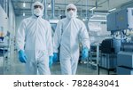 Small photo of Two Engineers/ Scientists in Hazmat Sterile Suits Walking Through Technologically Advanced Factory/ Laboratory. Clean High-Tech Environment with CNC Machinery.