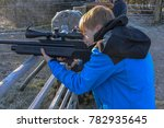 Close-up of a teenage boy firing an air rifle in the countryside on a cold, frosty day - stock photo