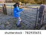 Landscape shot of teenage boy firing an air rifle on farmland on a cold, frosty day - stock photo